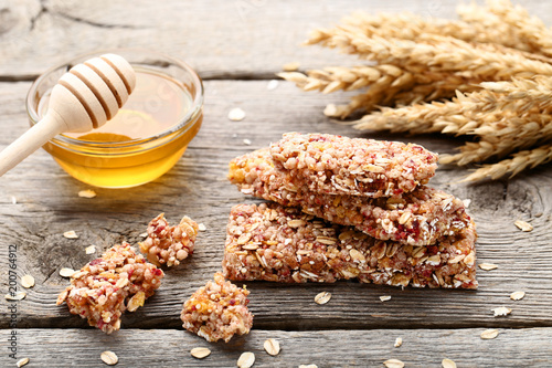 Tasty granola bars with honey in bowl and wheat ears on wooden table