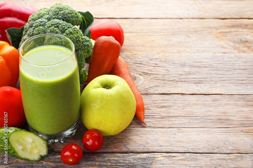 Vegetables smoothie in glasses on grey wooden table