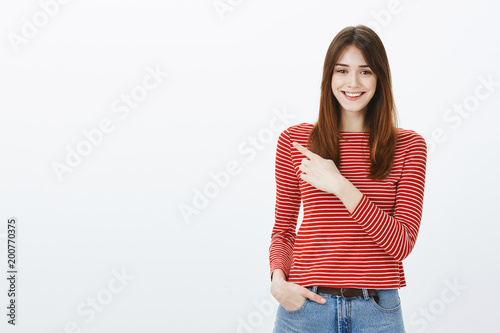 Pleasant attractive girl showing way out. Portrait of friendly confident european girlfriend with positive attitude, pointing at upper left corner and smiling happily, indicating at excellent place