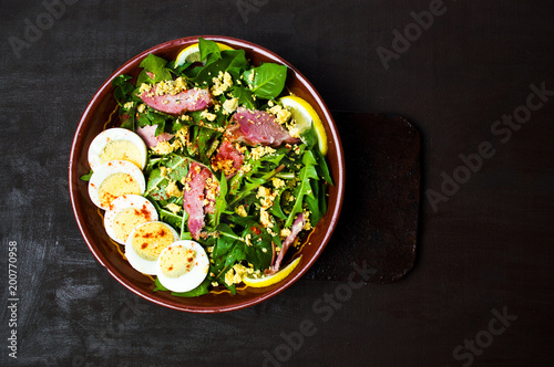 Dandelion salad with eggs meat and lemon in a bowl - 200770958