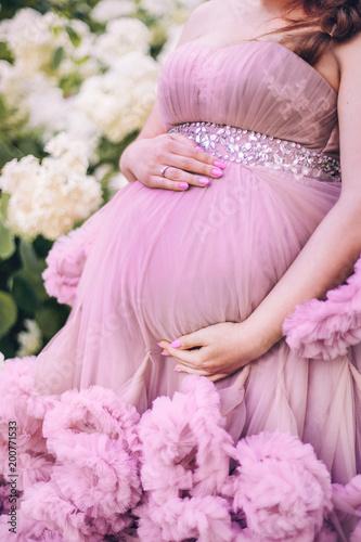 kobieta w ciąży stoi w różowej sukience z plisami w ogrodzie
