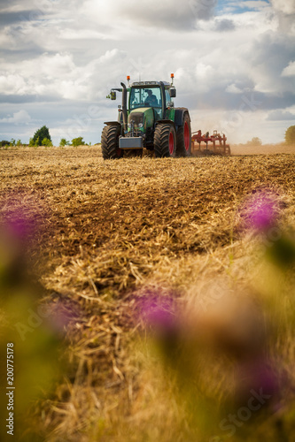 Aluminium Trekker A tractor ploughing a field of crops. Shallow depth of field with selective focus on the tractor.
