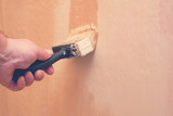 hand holding paintbrush and repainting wall, toned, copy space - 200776107
