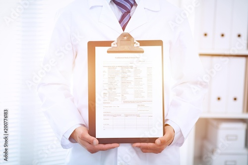 Foto Murales Unknown male doctor standing straight while holding medical form. Medicine and health care concept