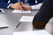 Group of business people and lawyer discussing contract papers sitting at the table, closeup. Businessman is signing document after agreement done
