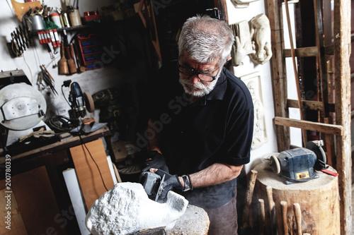 Starszy mężczyzna pracuje na marmurowej rzeźbie w jego warsztacie.