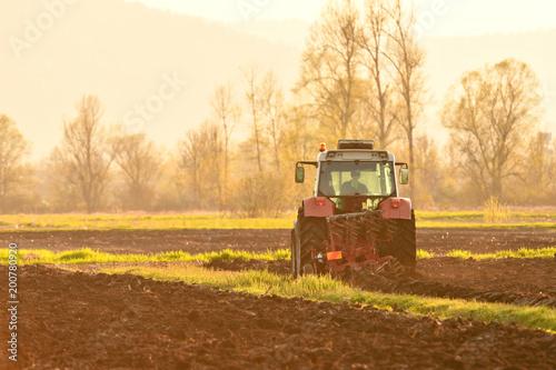 Fotobehang Trekker Farmer plowing soil at sunset in spring time