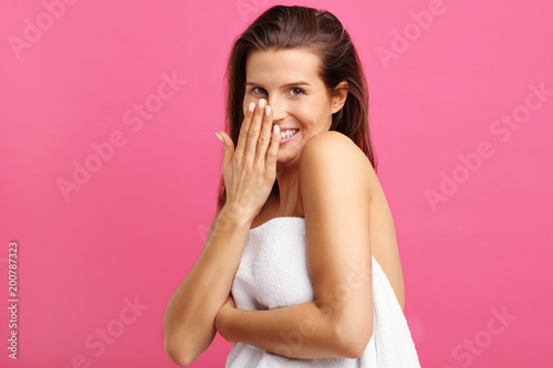 Beautiful woman in towel isolated over pink background