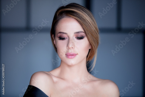Foto Murales Young woman with makeup in black dress in grey background