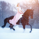 Young woman in pink dress galloping horseback on winter field. Romantic or historical equestrian background with copy space - 200792302