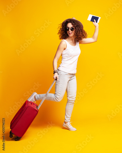 Woman traveler with suitcase on color background.