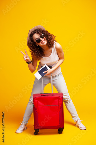 Foto Murales Woman traveler with suitcase on color background.