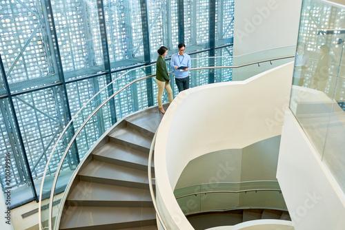 Wnętrze przestronnego biurowca ze spiralnymi betonowymi schodami i stylowym designem, dwóch kolegów zapakowanych w dyskusję projektową