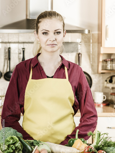 Woman in kitchen having many vegetables