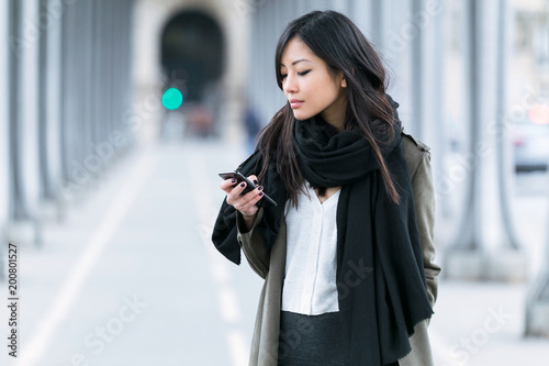 Concentrated asian young woman using her mobile phone in the street.