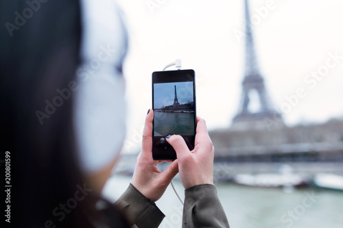 Back view of woman taking photograph of Eiffel tower from the river Seine in Paris. - 200801599
