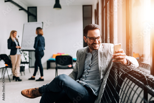 Close-up image of smiling businessman using cellphone in the meeting room.