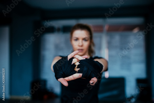 Woman stretching hands with boxing bandage toward camera.