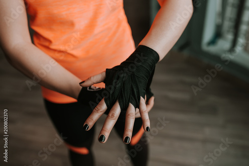 Poster Close-up image of female hand with black strap. Preparing for boxing.
