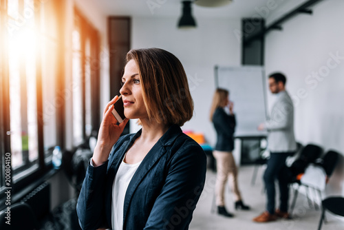 Portrait of a beautiful business woman talking on a phone in the office with collegues at the background.