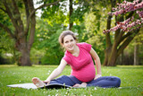 Pregnant woman exercising in the green park - 200804950