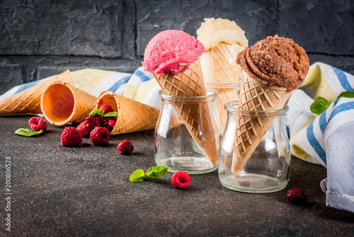 Foto Murales Summer sweet berries and desserts, various of ice cream flavor in cones pink (raspberry), vanilla and chocolate with mint on dark background copy space