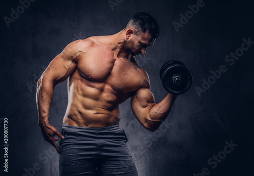 Poster Tall stylish shirtless bodybuilder dressed in sports shorts, doing exercise on a bicep with a barbell, standing in a studio.