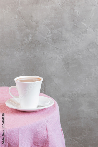 Wall mural Background with white cup of tea or milk on the table coated with pink tablecloth