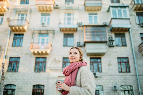 Portrait of young beautiful woman against residential building