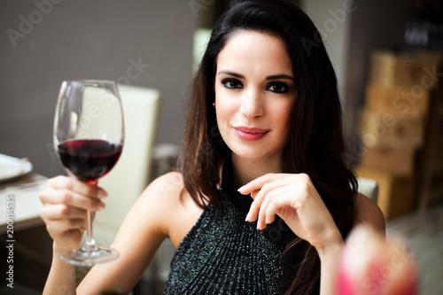 Foto Murales Woman holding a glass of red wine