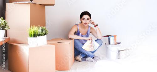 Kobieta wybiera farba kolor od swatch dla nowego domowego obsiadania na drewnianej podłoga. Kobieta w domu