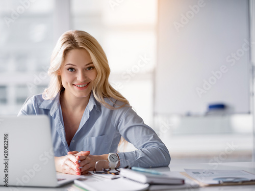 Foto Murales Waist up portrait of polite office worker listening to client attentively. She is looking forward and smiling. Woman is sitting at desk near laptop. Copy space