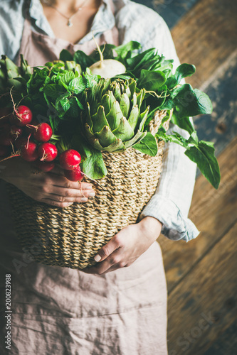 Female farmer wearing pastel linen apron and shirt holding basket with fresh seasonal vegetables in her hands, selective focus. Organic produce or local market concept
