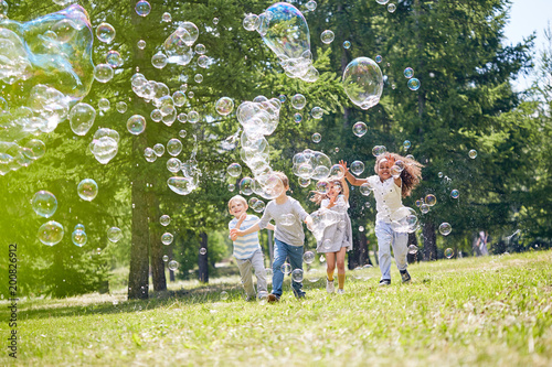 Group of cheerful little friends with wide smiles on their faces catching colorful soap bobbles while enjoying warm summer day outdoors