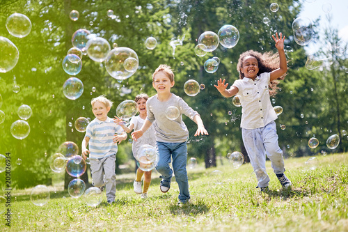 Foto Murales Multi-ethnic group of little friends with toothy smiles on their faces enjoying warm sunny day while participating in soap bubbles show