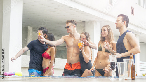 Foto Murales friends having party and dancing in a swimming pool - Fashion of summer beach bikini slim muscle women and men people enjoying vacation in a tropical resort hotel with beverage of bottle of beer