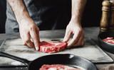 Man preparing beef steak on wooden table - 200839717
