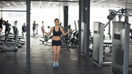 Active sport woman warming up with jumping rope, gym workout, healthy lifestyle © motortion