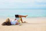 Man working on laptop computer while relaxing on the beach