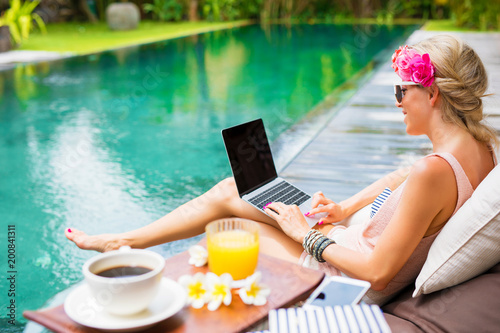 Foto Murales Woman working on laptop while sitting by the pool