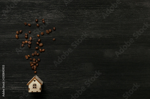 Foto op Aluminium Koffiebonen Coffee house and smoke from a pipe made of coffee beans isolated on black wooden table background with copy space. Coffee abstract background. Coffee shop.
