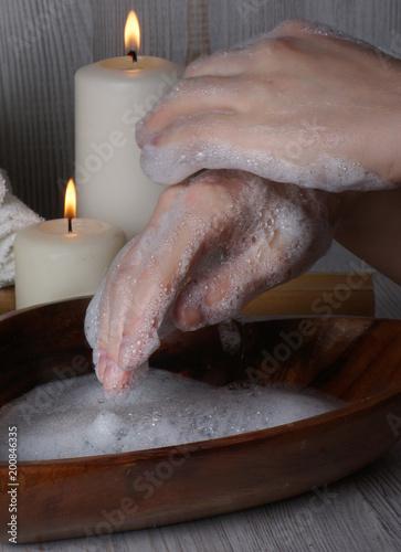 Kobiece ręce, pokryte pianką mydlaną obok palących się świec w biurze do zabiegów spa