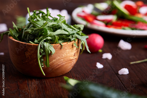 Creative fresh vegetable salad with ruccola, cucumber, tomatoes and raddish on white plate, selective focus