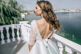 Beautiful bride in a fashion dress stands with her back - 200849595