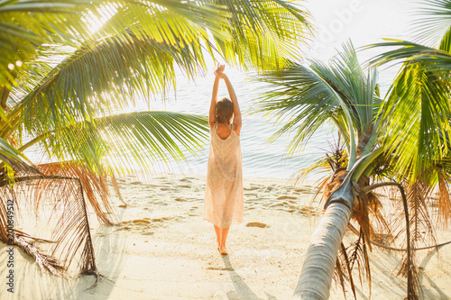 back view of woman stretching between palm trees on seashore