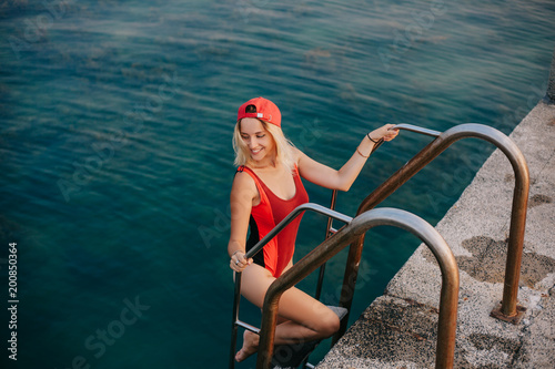 Foto Murales beautiful girl in swimsuit going out from ocean at public beach