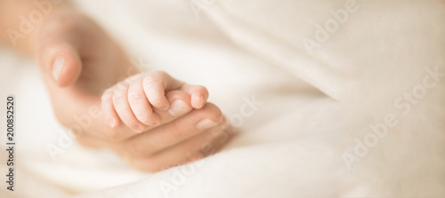 Female hand holding her newborn baby's hand. Mom with her child. Maternity, family, birth concept. Copy space for your text. Banner