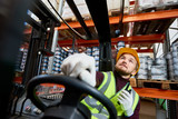 Low angle portrait of young warehouse worker sitting inside forklift moving goods from tall storage shelves and holding portable radio, copy space - 200858922