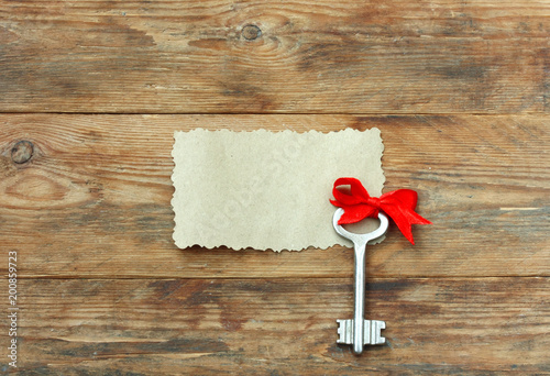 key with red bow silk ribbon, on wooden table