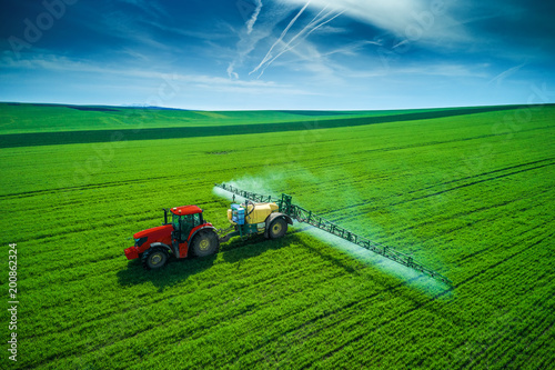 Zobacz obraz Aerial view of farming tractor plowing and spraying on field